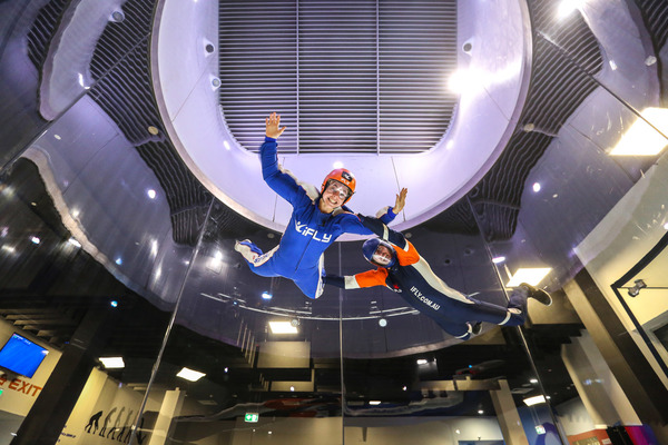 Indoor skydiving view from below of a person in blue jump suite and helmet and a person in black jump suite and helmet floating in mid air